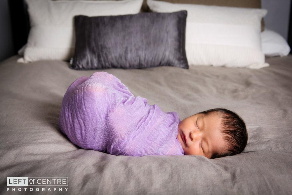 newborn sleeping on parents bed