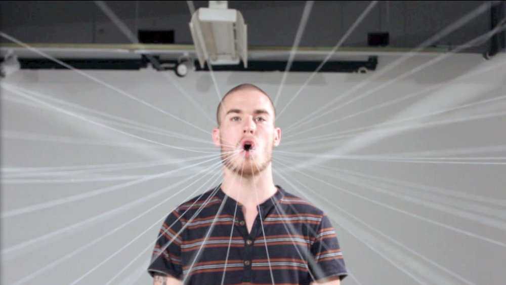 Tyler O'Brien Introduction to Textiles , 2014  Virginia Commonwealth University   Hybridity /  Use disparate materials, processes or concepts to create a unified, hybrid whole.  Tyler filmed himself performing speech exercises. Strings attached his tongue to a large canvas, the surface of which exaggerated his movements.