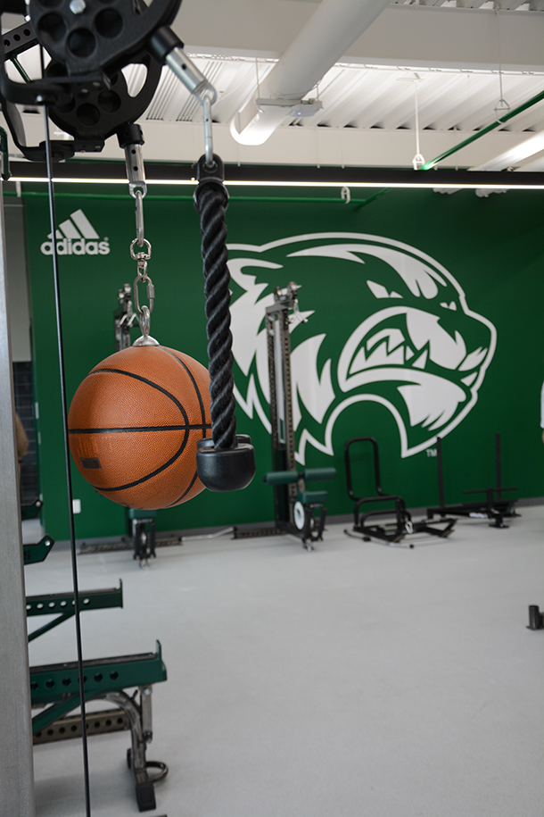 The Travis Hansen Strength & Conditioning Center has a net mesh separating the weight room from the basketball court.