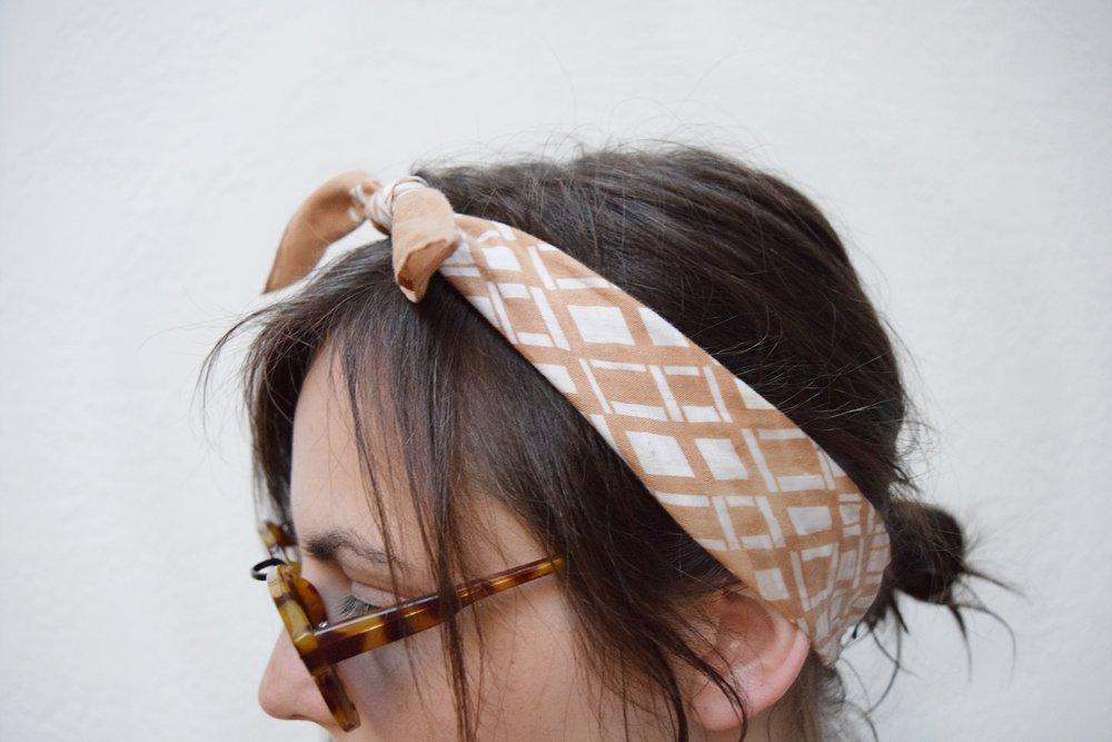 nude head scarf messy bun hairstyle and vintage tortoiseshell sunglasses