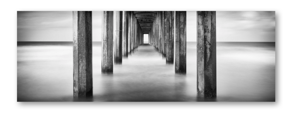 """Scripps Pier - La Jolla, California    This is a very famous and iconic photography destination. But being the desert dweller that I am, and having a much grander affinity for the mountains than the sea, I do not get to the ocean very often. But when I  am  there I do like to go and try to capture something that really moves me.   I ought to go to the ocean and photograph more often   I was down in San Diego for a photography convention in February 2015 and wanted to create some photographs for myself while I was there. I had done some research of photo destinations near where I was staying prior to my trip and this image kept popping up in my browser.  I was immediately drawn to the symmetry of the pier's pylons. Planting my tripod right in the perfect middle of the pier allowed me to center up the far end """"opening"""" of the pier. It felt like a portal to another dimension!   I wanted something different - something I had imagined in my mind's eye but hadn't actually seen created yet. I'd seen several images of this pier from this perspective - dead center - but none of them in black and white and none of them in a panoramic perspective nor with a long exposure.  It actually wasn't an easy shot to get! There was a lot of seaweed gathered against some of the pylons closer to the beach and I had to put the tripod in the waterline. But as the sea ebbed and flowed with the tide it would wash away the sand the tripod was on and blur the image.    81 seconds later…    Finally  I was able to get a capture where the tripod didn't move and I had tack sharp exposure on the pylons from front to rear with smoothed out ocean. Post-processing in Lightroom allowed me to convert to black and white and make the 1:3 crop that you see presented.   The reason I call this image 'Tunnel Vision' is because once I had 'the shot' I packed up my gear and left, happy with what I had on the back of the camera. I didn't even explore a single alternate perspective! Tunnel Vision, indeed. I guess """