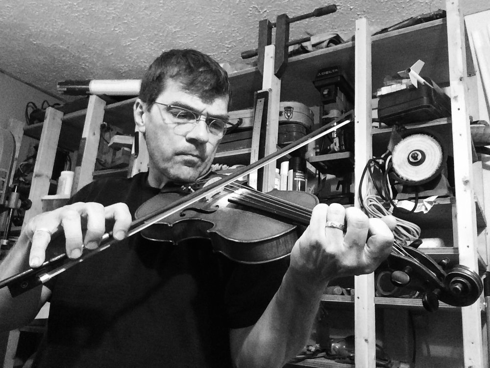 """Colin Carrigan was born with a fiddle under his chin."" Such an illustrious claim could have been made, had the medical wisdom of the 1970s not deemed this procedure too risk-laden. Instead, Colin and his fiddle were acquainted in boyhood years—without medical supervision—under the tutelage of Newfoundland fiddle legend, Kelly Russell. Quick was his ascension into the rich Anglo/Irish musical tradition of his homeland, and his early apprenticeship saw him sharing the stage with the fabled likes of Emile Benoit and Rufus Guinchard. By first chin-scruff, Carrigan was forming bands and busking in the streets of downtown St. John's, playing polkas and slides, jigs and reels, come-all-ye's and whack-fol-lol-di-ra's.  Colin has since conducted a long career of teaching, recording, performing and touring. His repertoire and style are a fusion of Newfoundland, Irish and Scottish music: one-hundred albums of which were ground smooth on turntables through his formative years. He is a luthier, teacher, and architect, and presently hosts several traditional sessions in his adopted home of Halifax, Nova Scotia. He remains a champion of the Good Tune."