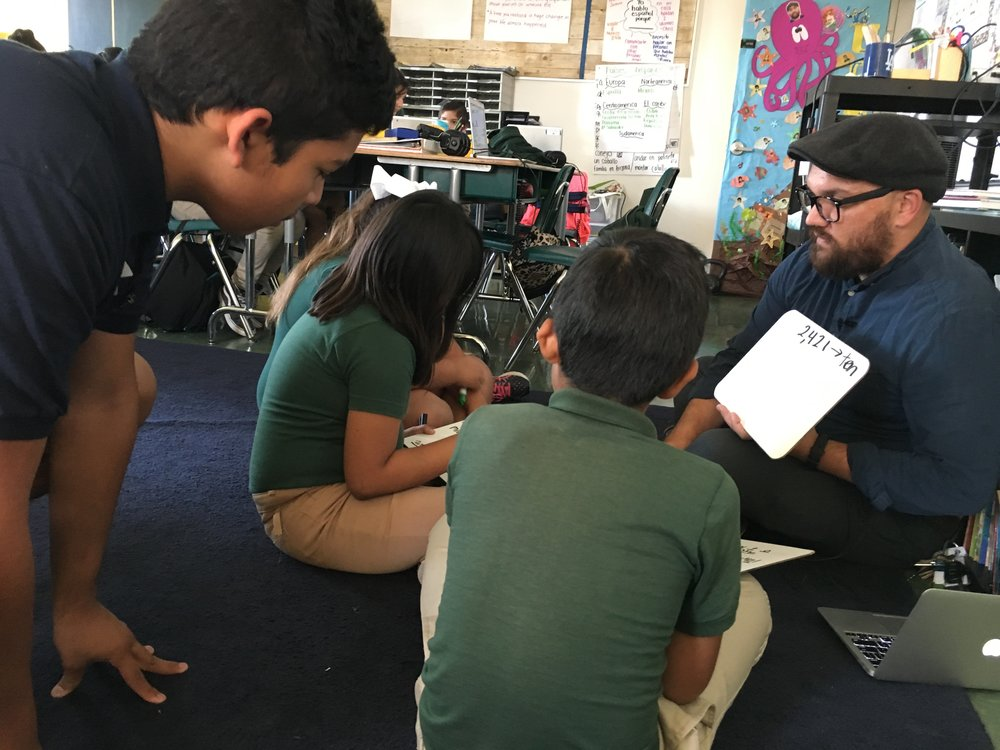 Julio joining a small group of students for math instruction with fourth grade teacher, Joshua Martinez.