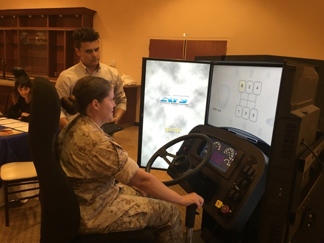 Gail Badell, Marine Air-Ground Task Force Planner, tests out her shifting skills on the ATS driving simulator available for service members at the Camp Pendleton hiring fair.