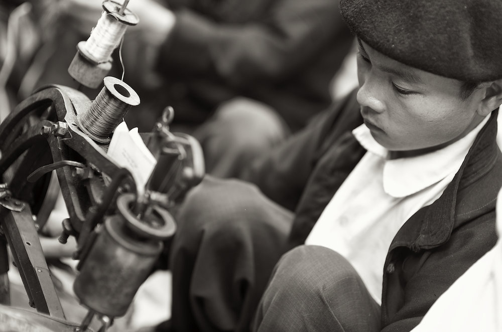 A young tailor in the Dong Van Market in Vietnam.  Image by New Orleans based travel photographer, Marc Pagani