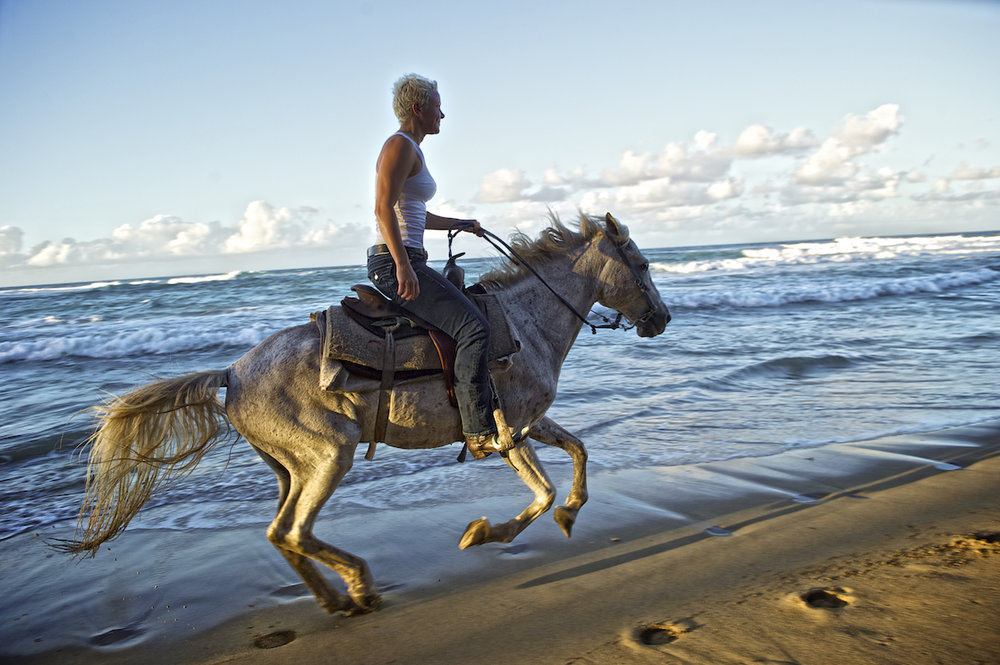 A woman rides a horse on the beach in the Dominican Republic. Image by New Orleans based travel photographer, Marc Pagani