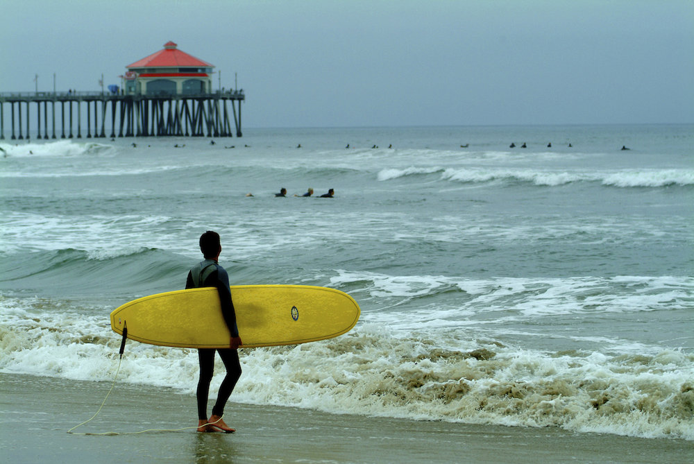 A surfer looks at the waves at Huntington Beach, California.  Image by New Orleans based travel photographer, Marc Pagani