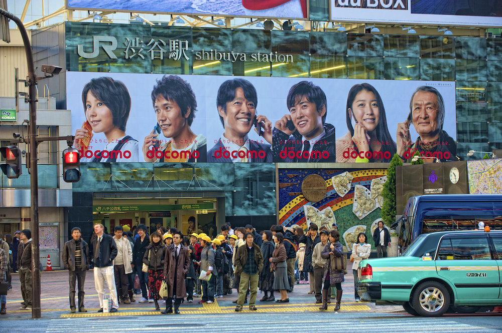 A billboard and office workers in Shibuya, Japan.  Image by New Orleans based travel photographer, Marc Pagani - marcpagani.com