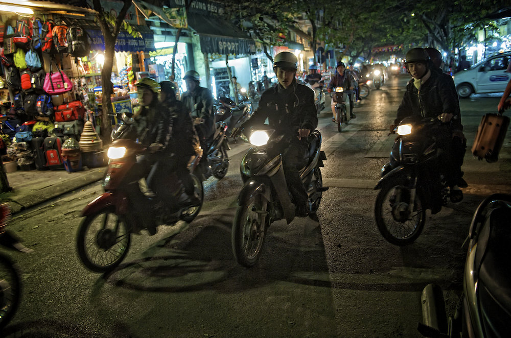 Motorcycle and scooter riders at night in Hanoi, Vietnam.  Image by New Orleans based travel photographer, Marc Pagani - marcpagani.com