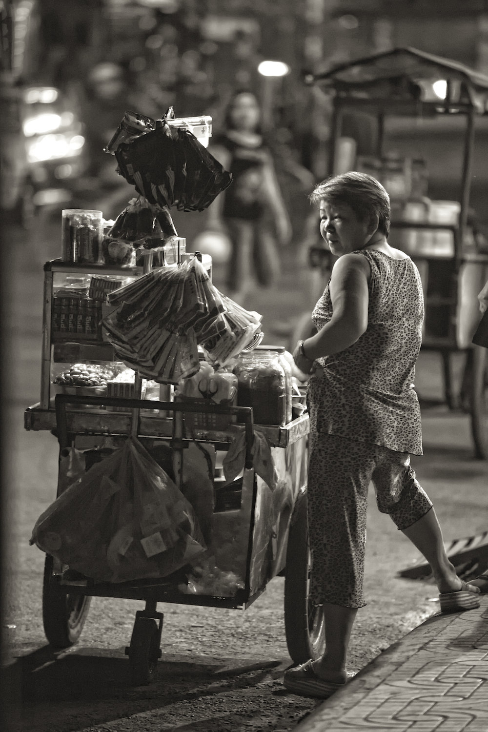 A woman sells her goods at night in Ho Chi Minh City, Vietnam.  Image by New Orleans based travel photographer, Marc Pagani - marcpagani.com