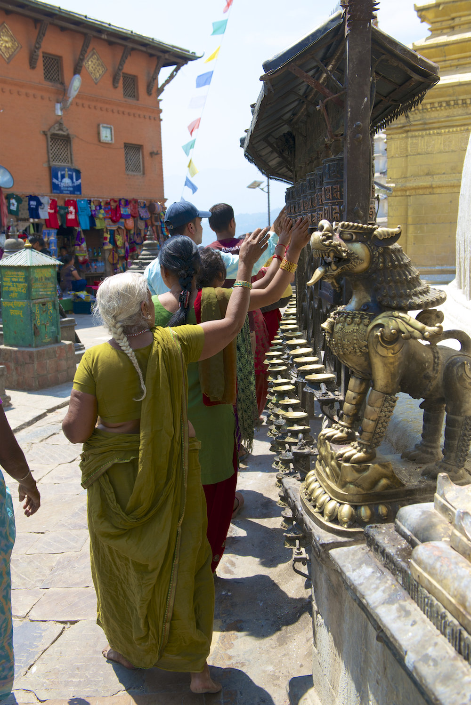 Buddhists pass by prayer wheels at Swayambhunath Temple in Kathmandu, Nepal.  Image by New Orleans based travel photographer, Marc Pagani - marcpagani.com