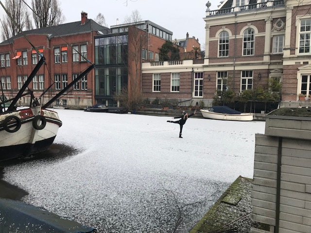 """Walking on the frozen canal outside of """"The Wittenberg""""in Amsterdam."""