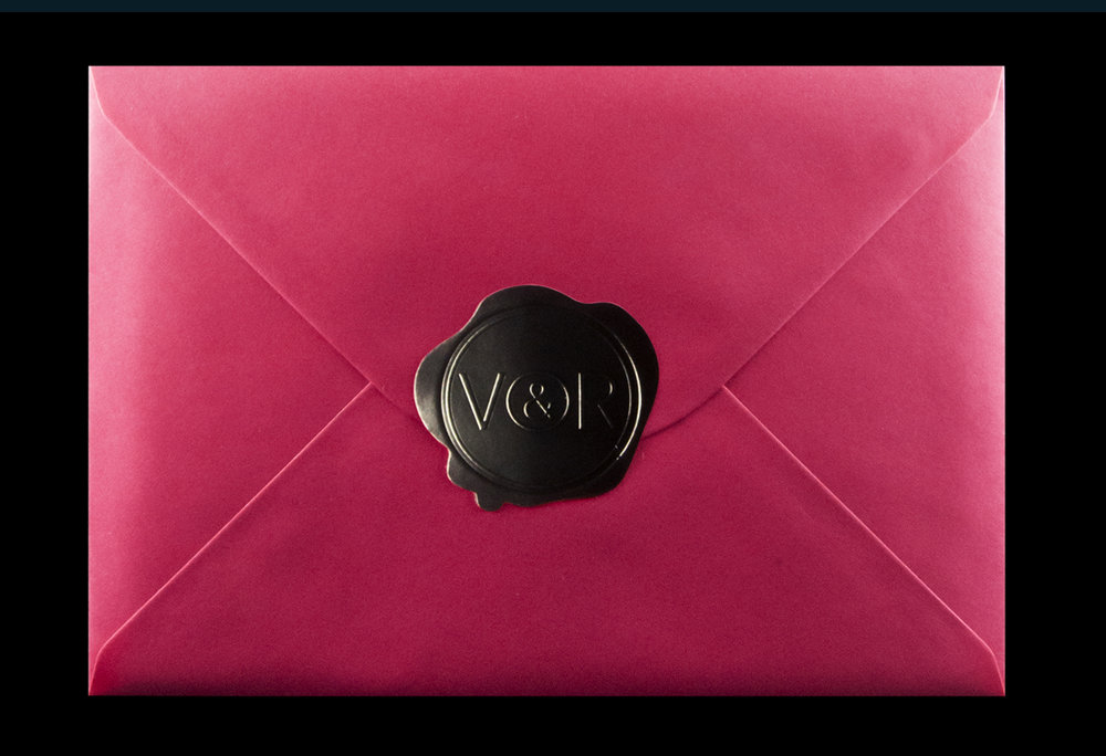 Pink envelope with imitation wax seal sticker.