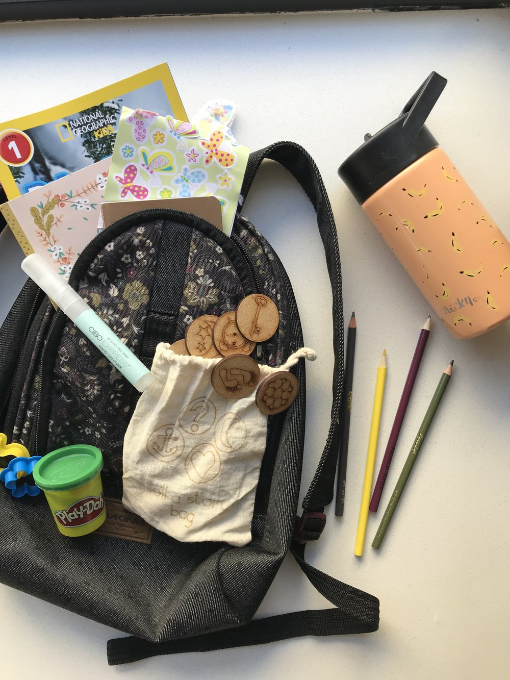 Little notebooks, a coloring book, pencils, reading material, stickers, playdough, spray hand sanitizer (my kids like to have their own hand sanitizer), a game that inspires creativity, water bottle. Not pictured: childs sleep mask which is a game changer. Some airlines actually hand these out.