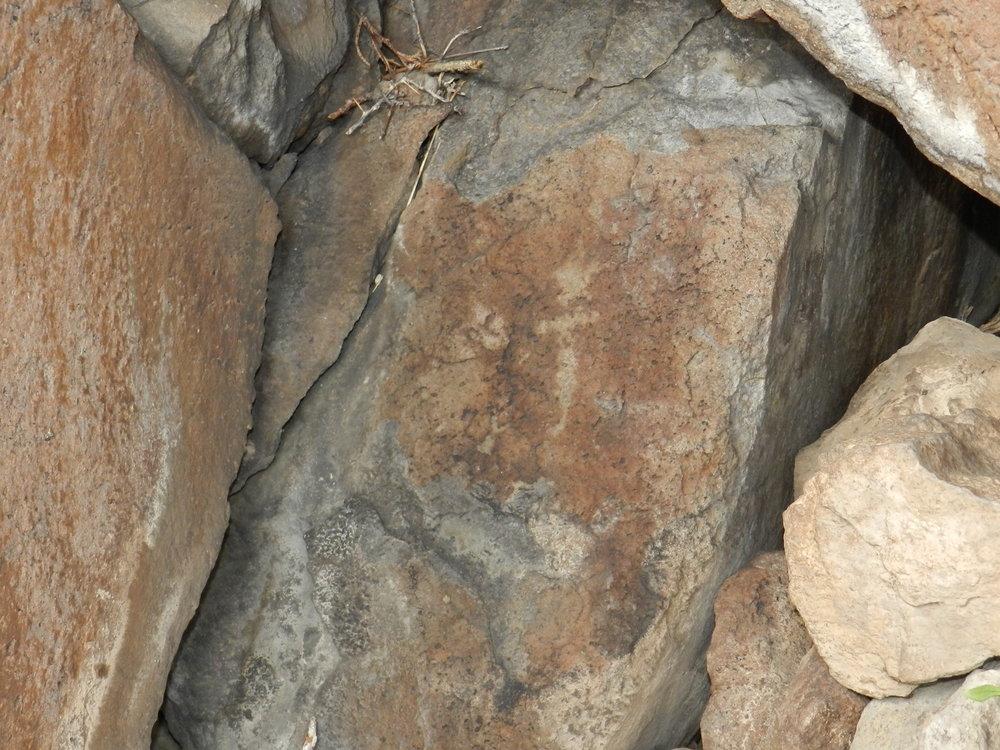 Iron oxide glyph on stone.