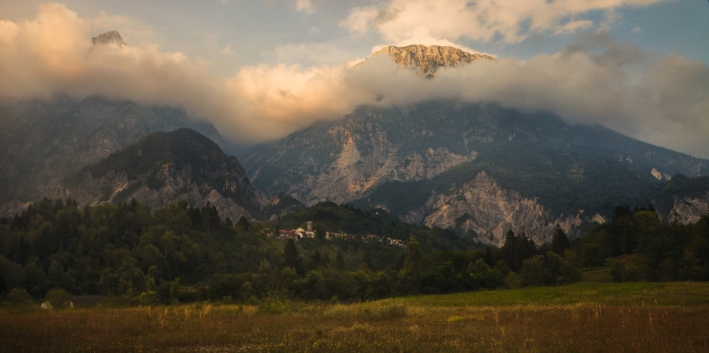 Mountain peaks covered in clouds at sunset at Barcis Lake, Italy. The face of the mountains above a quaint mountainside town peaks through the clouds and is lit by the warm sunlight.