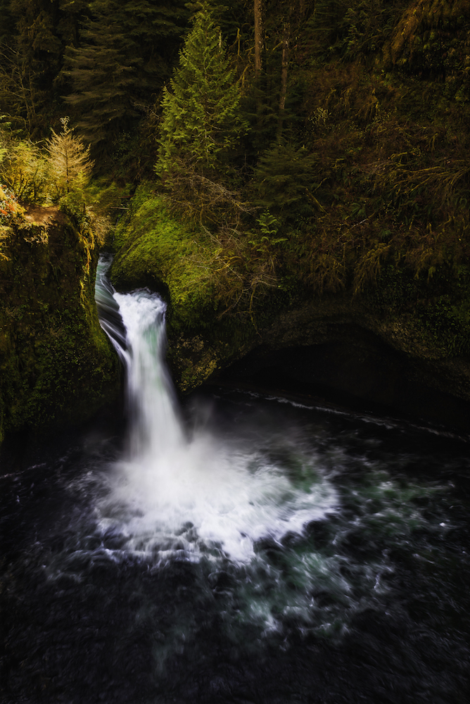 Punchbowl Falls, Eagle Creek Washington. Captured in autumn light the waterfall streams through the image.