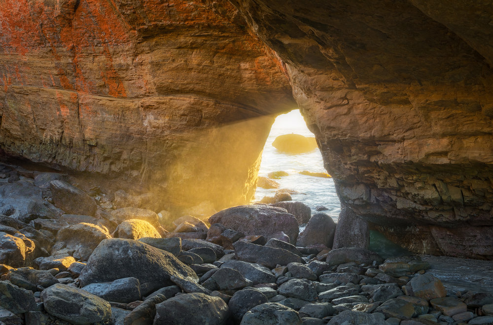 Photograph from Devil's Punchbowl in Oregon by Jason Matiatas captured at Sunset with the light rays shining through the cave opening.