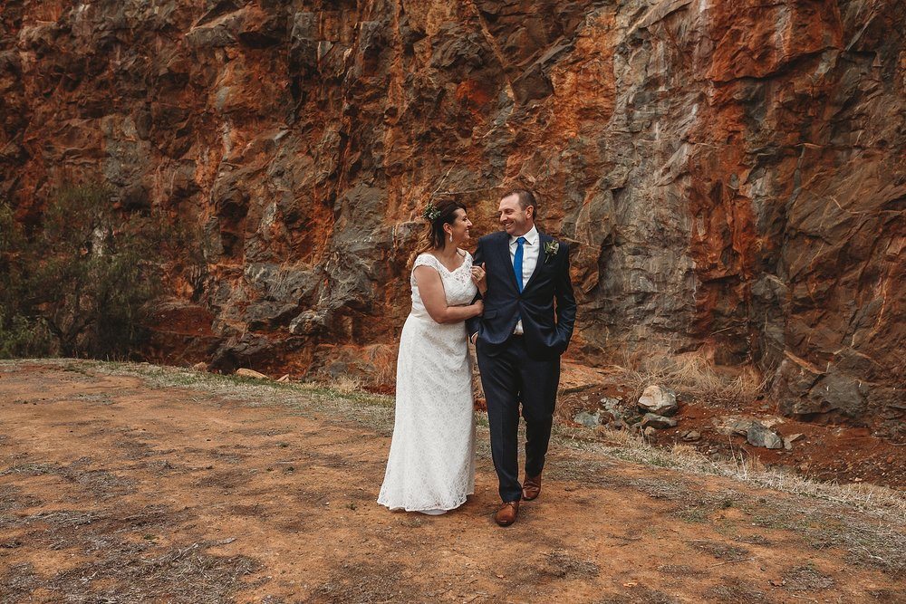 bride and groom walking and laughing at dookie quarry