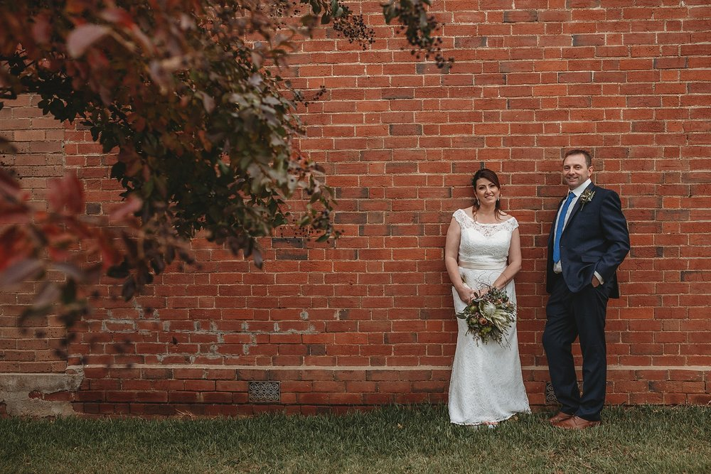 dookie shop wall with bride and groom leaning against it