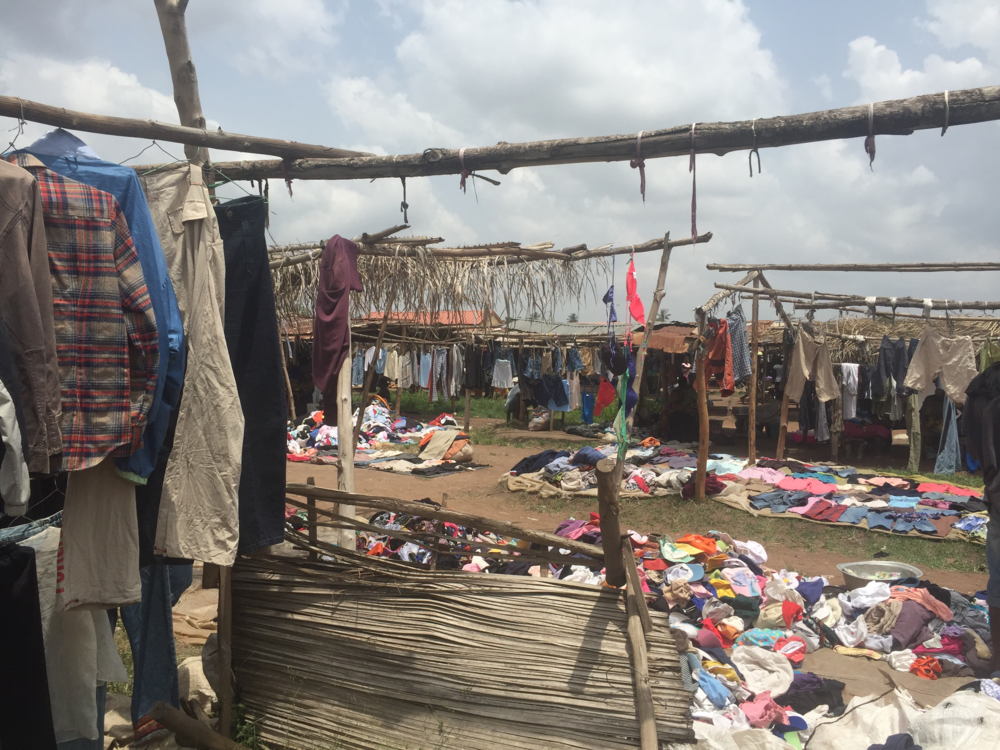 At the market in our village, Notse. The second-hand clothing section spans several field lengths and is packet full with mounds of clothing.