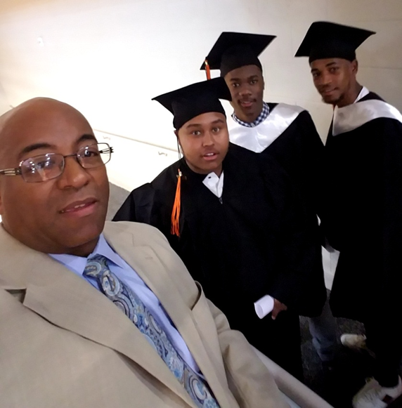 """Pictured is CEF Program Director Gerald Rocha with three graduates from STEM High School. The student in the center, Khalir Barrett, was one of the beneficiaries of the credit recovery program."""