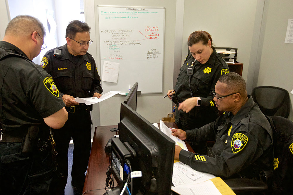 San Francisco lacks a fully interconnected criminal justice computer database that shares information in real time. Sheriff's deputies must still review paper instructions from the court. Photo by Kevin Hume.