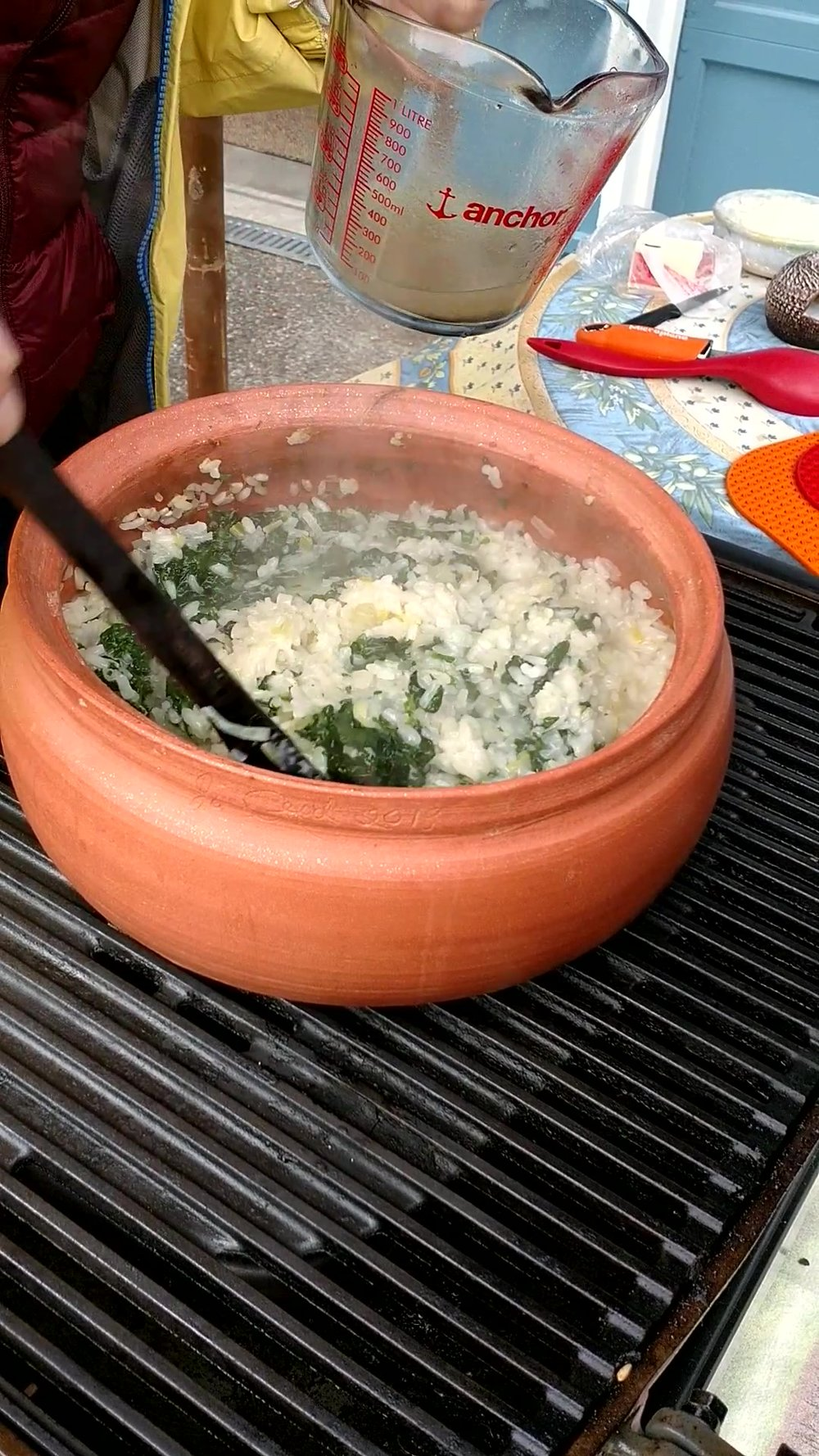 Making spinach risotto in a dutch oven on a propane grill.