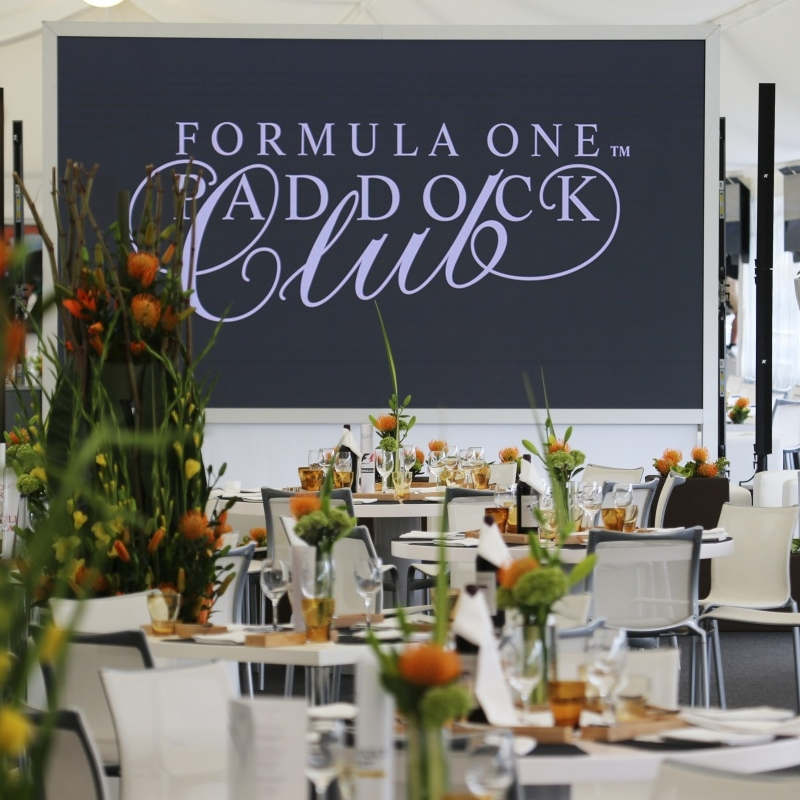 Paddock Club - Starting at £795 Per PersonExperience the luxury and elegance of the Formula One Paddock ClubTM as guests are treated to world-class gastronomy, high-octane race action and spectacular entertainment. Situated above the pit garages, the Formula One Paddock Club offers a privileged panoramic view of the Pit Straight, starting grid, race team hospitality suites and the Paddock.All Paddock Club suites have wall-to-wall windows overlooking the Pit Lane and are fitted with luxury furnishings and plasma screens for the live race feed. Guests can also enjoy an up-close view of the Formula One cars as they exit the Pit-Lane − mere metres away from the exclusive Paddock Club grandstand.