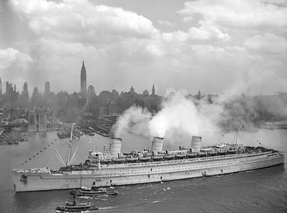 The Queen Mary outside New York City in grey military paint during WWII  Photo by USN via Wikimedia Commons