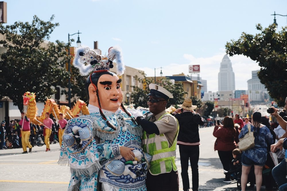 Man in costume posing for a photo with a police officer in the 2019 Chinatown Parade