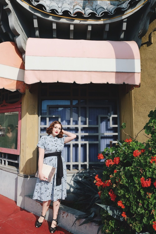 Rachel in vintage blue dress standing in front of Hop Louie restaurant in Chinatown