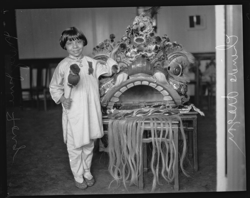 Mary Jane Fong holding a gong stick and standing next to a Chinese lion in Chinatown, Los Angeles. Photo via  Los Angeles Times  (1927)