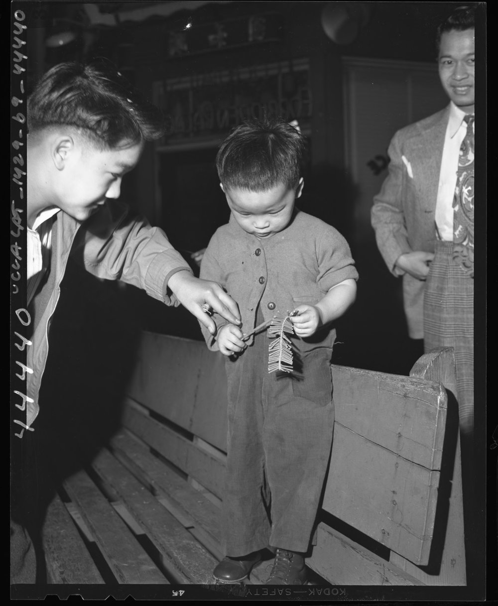 Roland Soo Hoo, 3, armed with punk stick and firecrackers, gets instructions from an older brother in preparation for celebrating Chinese New Year's Day. Photo via  Los Angeles Times  Photographs Collection (1947)