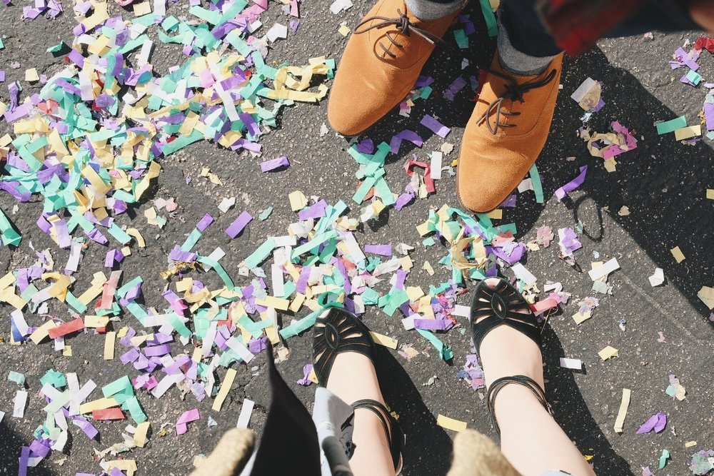 Looking down on feet of man and woman with multicolored confetti all around