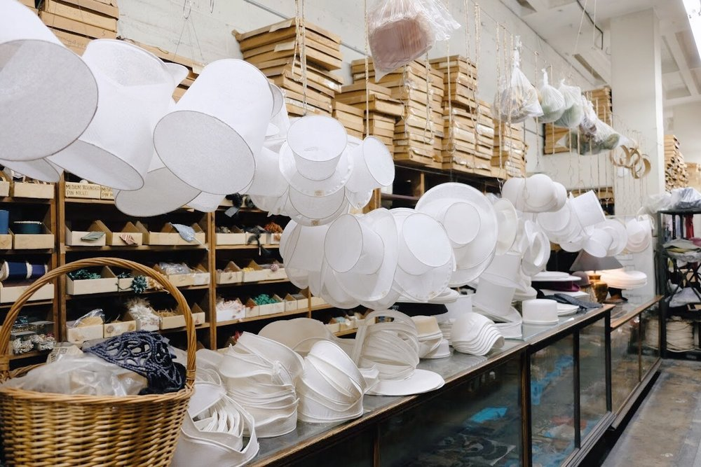 Buckram hat frames hanging above glass display cases filled with feathers and other hat supplies at California Millinery Supply Co.