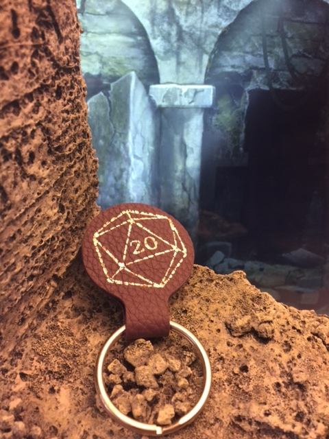 D20 Leather Key Ring Fob – Elderwood Academy  We can't keep you from losing your keys, but we can make them look great wherever they are. This time the woodsmiths at Elderwood Academy work their magic with leather. This key ring fob is handcrafted from the genuine leather stock they use to make their amazing Codex and Scroll Cases. It features a metallic pressed D20 design.  Retail value: $8 from elderwoodacademy.com