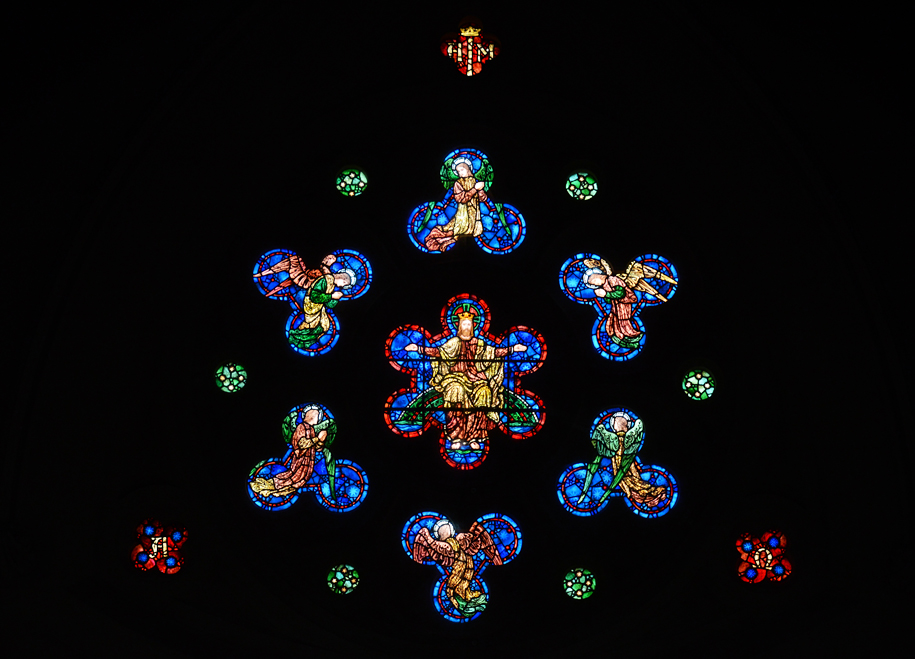 West Window - Another example of stained glass brilliance, the west or rose window is best viewed from the top of the chancel steps. Wheel shaped in design, it features a central light with Christ seated on a rainbow surrounded by angels. This work of art is at its best in the late afternoon light. The shape of the angel lights has suggested to some the idea of angels on bicycles!