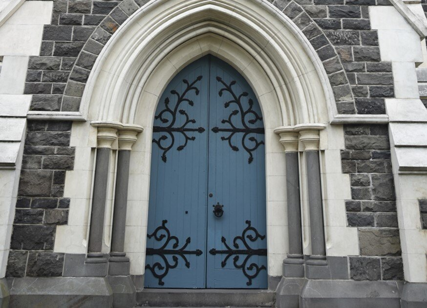 West Door - The entry porch was an addition to the church in 1961 to mark the Parish centenary. The screen at the entrance to the church was presented by Shona Howell in 1962 in memory of her parents, George and Nellie Rhodes, early Timaru settlers whose family the land on which the church sits.