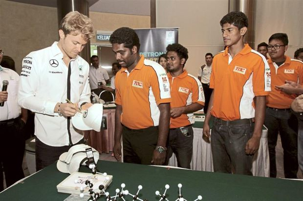 Could you sign this?: Rosberg (left) signing the cap for Aristo (second from left) while Ashik (third from left) waits his turn.  Image source:  The Star Online