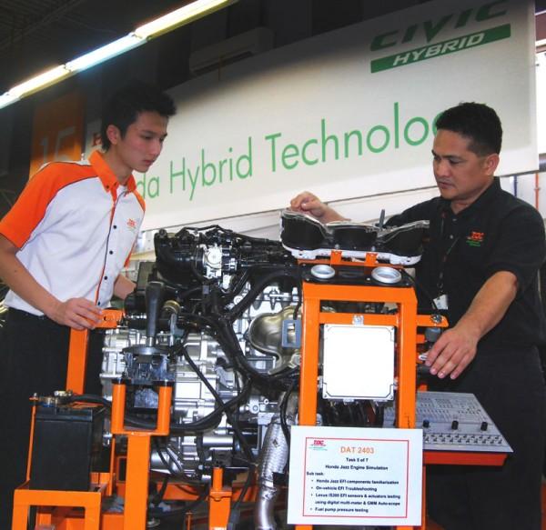 Cabas explaining to Chen how to diagnose the faults using the Honda Jazz engine simulator.  Image form: zerotohundred.com