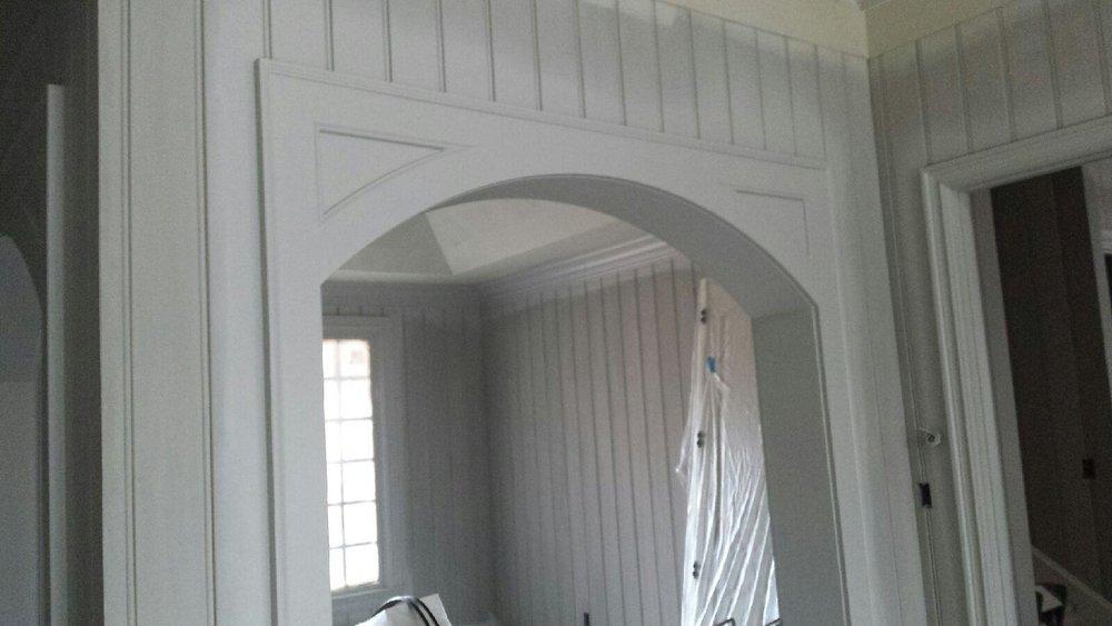 Coastal style segment arch with corner wall paneling