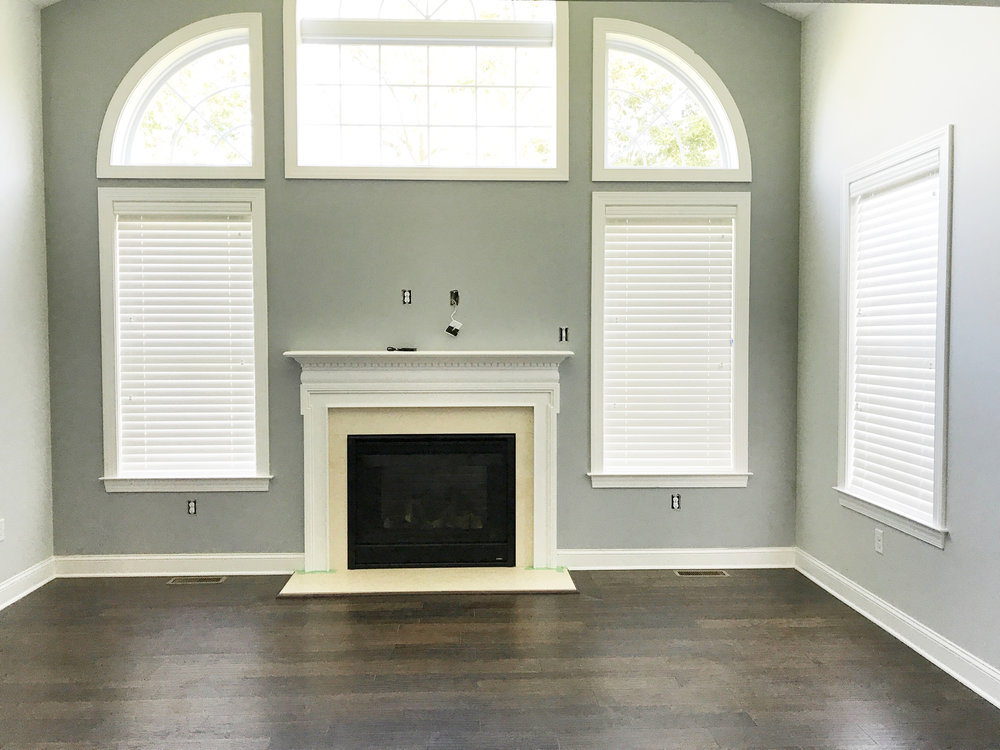 Custom window blinds surrounding fireplace in living room by 3rdGenBlinds