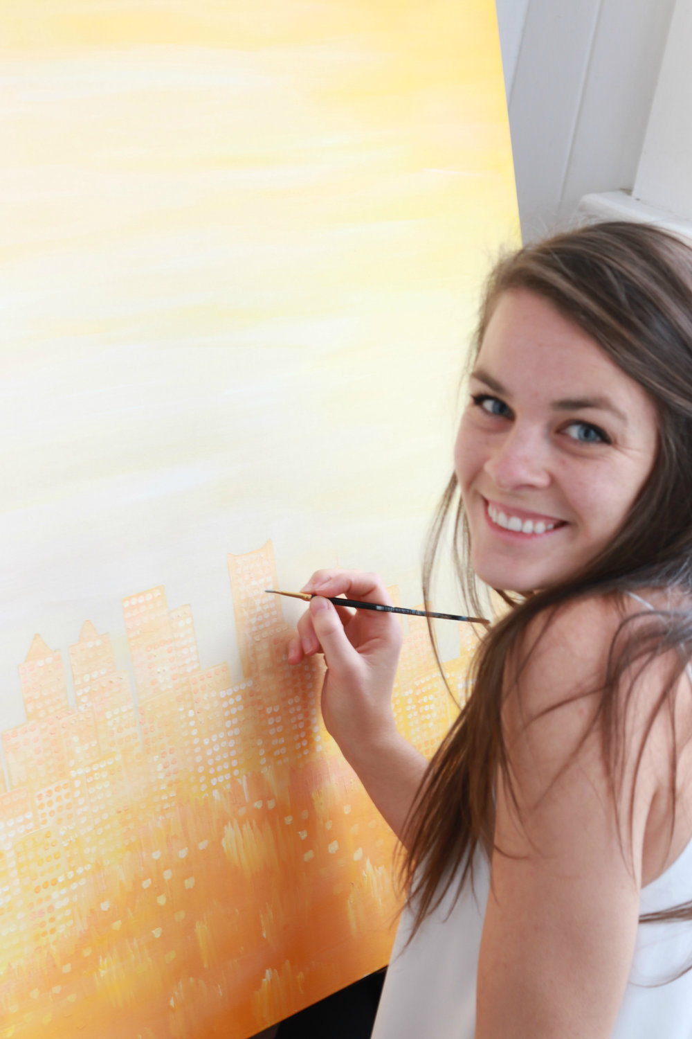 One of my goals for the most recent photo shoot was to get some behind-the-scene shots of me completing a painting. It might be hard to tell in this photo, but this painting is of the Calgary skyline.