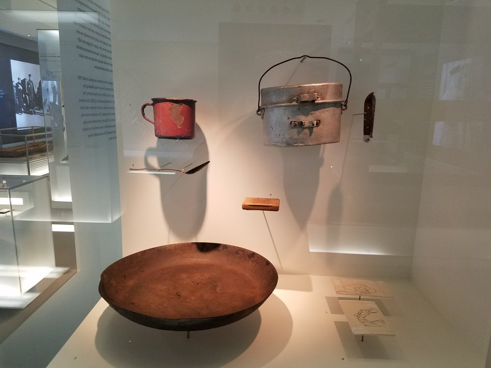 Utensils used to prepare meals in the prisoners' kitchen at Sachsenhausen. A cooking bowl, bottom centre; a coffee mug on the top left, and a large tin on the top right. -