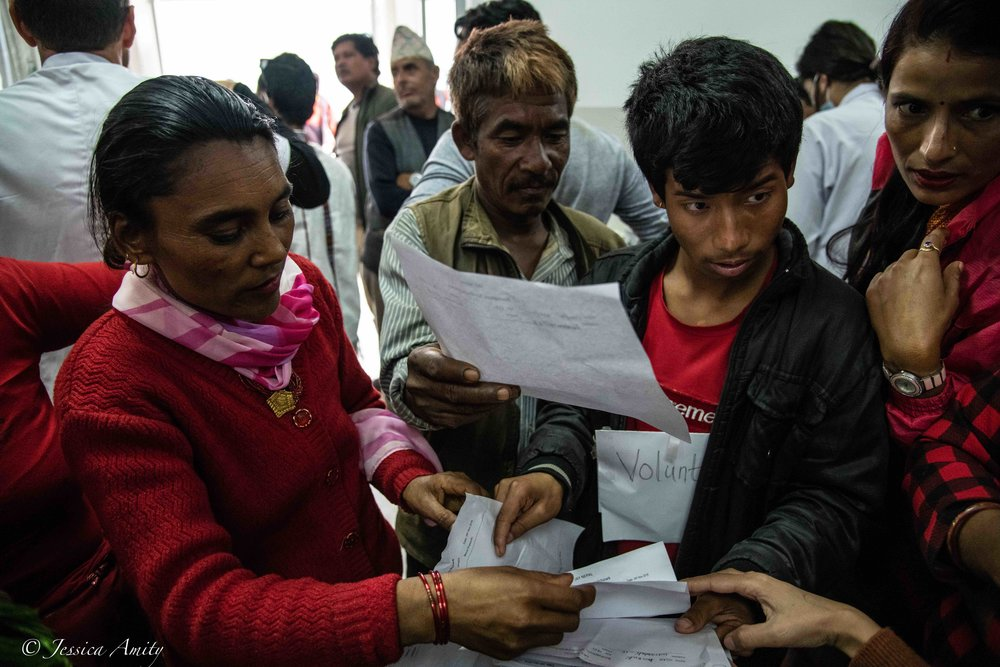 Jay Nepal International and village volunteers sorting through patient records.