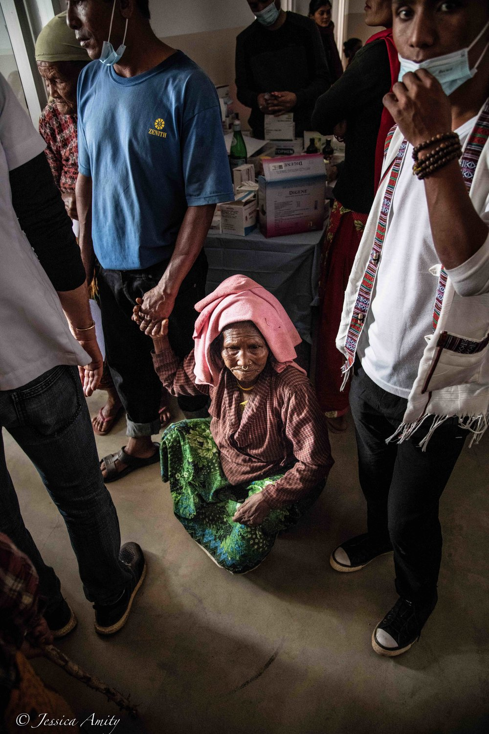 Although you are unable to see from this photo, the woman pictured is unable to walk. Her feet and toes are all misaligned. I was told later that this might have been a result of a broken bone that was not treated and thus had not healed correctly. She holds her sons hand for support before seeing the doctor.