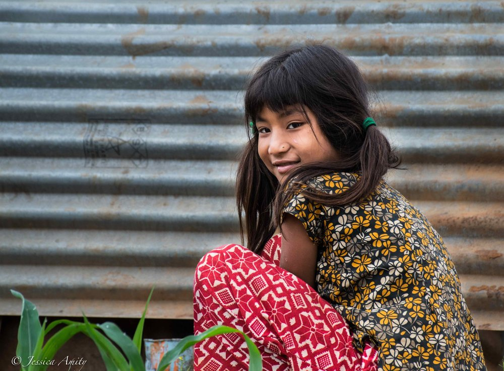 A young girl sits outside her home made from corrugated iron sheets.  Since the earthquake in 2015 many of the Majhi community in Bodgaun are still living in temporary shelters.