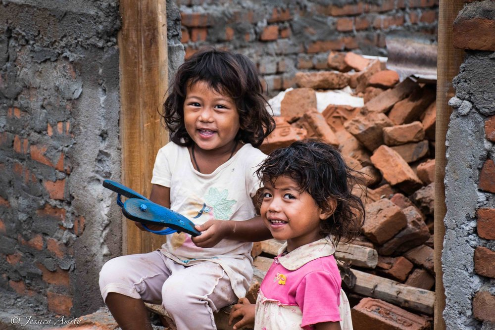 Two little girls sitting in what will be the doorway of their newly constructed home.