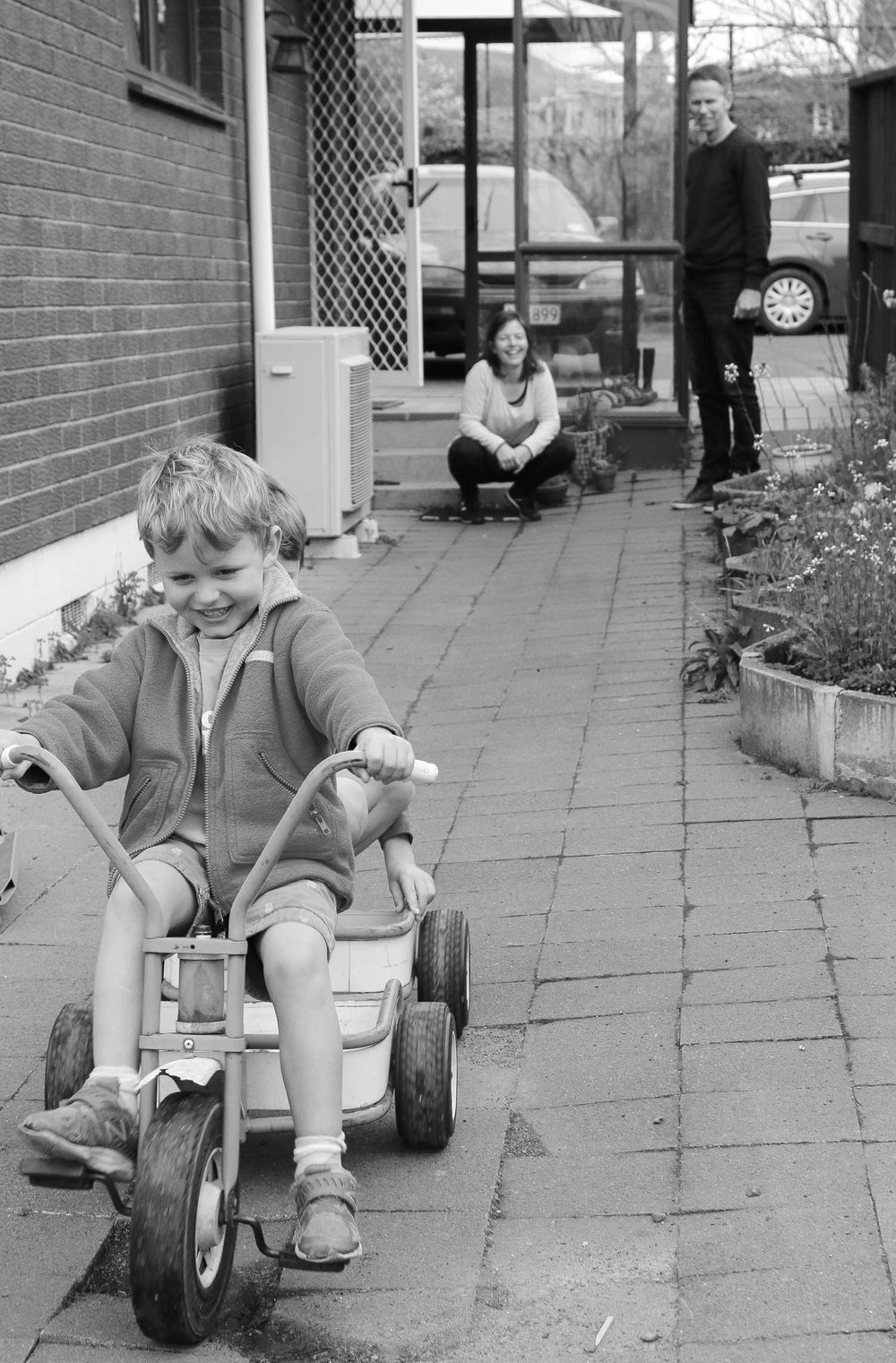 boy-playing-on-trike-mum-sitting-in-background-watching-and-smiling-black-and-white.jpg